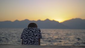 Eenzaam kind op het strand bij zonsondergang stock videobeelden