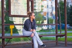 Eenzaam meisje die op vervoer bij de bushalte wachten Royalty-vrije Stock Fotografie