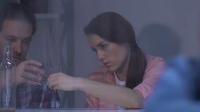 Eenzaam meisje die in venster, ouders kijken die alcohol op achtergrond, verslaving drinken stock video