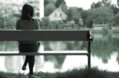 Eenzaam meisje door het meer Stock Afbeeldingen