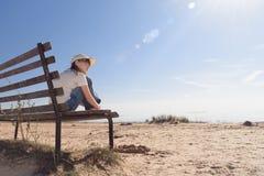 Eenzaam meisje met glazen die op een bank op de kust en blikken droevig in de afstand situeren stock foto