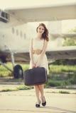 Eenzaam meisje met koffer bij dichtbijgelegen vliegtuig. royalty-vrije stock afbeelding