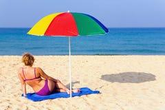 Eenzaam meisje op het strand onder een kleurrijke paraplu royalty-vrije stock afbeeldingen