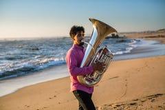 Eenzaam musicusspel aan tuba op de Overzeese kust stock foto's