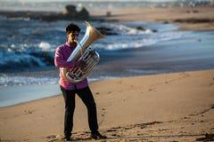 Eenzaam musicusspel aan tuba op de Overzeese kust stock foto