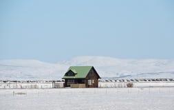 Eenzaam traditioneel Ijslands die huis door sneeuwlandschap wordt omringd Stock Afbeeldingen