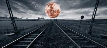 Eenzaam treinspoor en een surreal volle maan stock afbeeldingen