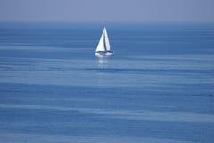 Eenzaam wit zeil bij oneindige oceaan Stock Foto