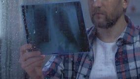 Eenzaam ziek mannetje die in hopeloos, eindkankerstadium van het longen x-ray gevoel bekijken stock footage