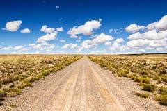Eenzaamheid bij de oneindige landweg in de woestijn met wolken Royalty-vrije Stock Foto's