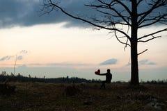 Eenzaamheid Eenzaam Meisje in een eenzame boom tegen de hemel Op de achtergrond van de zonsopgang Rood hart ter beschikking royalty-vrije stock afbeeldingen
