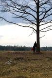 Eenzaamheid Eenzaam Meisje in een eenzame boom tegen de hemel Op de achtergrond van de zonsopgang Rood hart ter beschikking stock afbeelding