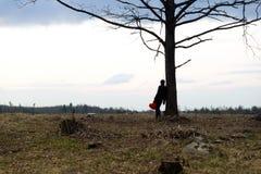 Eenzaamheid Eenzaam Meisje in een eenzame boom tegen de hemel Op de achtergrond van de zonsopgang Rood hart ter beschikking royalty-vrije stock foto