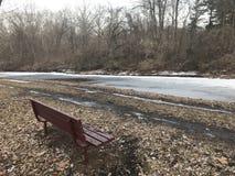 Eenzame bank door de ijzige rivier stock foto