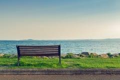 Eenzame bank op overzeese kust stock foto's