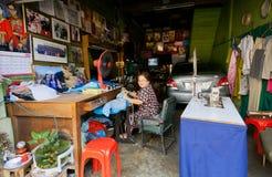 Eenzame bejaarde dame naaiende kleren in een garagehoogtepunt van verschillende dingen Stock Afbeeldingen