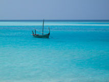 Eenzame boot op blauwe overzees stock foto