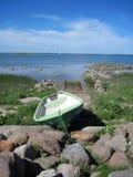Eenzame boot op het strand amond de stenen Stock Foto