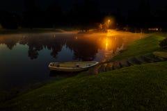 Eenzame boot op meer met mist Stock Afbeeldingen