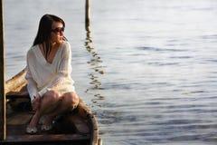 Eenzame dame die op boot zonsopgang kijkt stock afbeeldingen