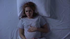 Eenzame denkende vrouw die in bed het strijken buik, hopeloosheid, depressie schreeuwen stock videobeelden