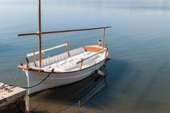 Eenzame die boot aan het dok wordt gebonden Stock Foto's