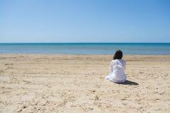 Eenzame donkerbruine vrouw met lobghaar op een strand en het kijken op overzees Achter mening Stock Afbeelding