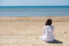 Eenzame donkerbruine vrouw met lobghaar op een strand en het kijken op overzees Achter mening Royalty-vrije Stock Afbeeldingen
