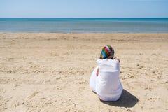 Eenzame donkerbruine vrouw met sjaalzitting op een strand en het kijken op overzees Achter mening Stock Afbeelding