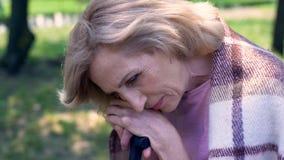 Eenzame droevige grootmoederzitting in verpleeghuistuin, gebrek aan steun, geheugen stock fotografie