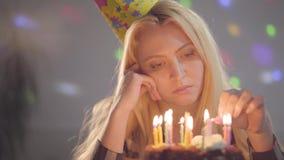 Eenzame droevige meisjeszitting voor de kaarsen van weinig cakeverlichting De ongelukkige vrouw heeft verjaardagspartij Concept v stock footage