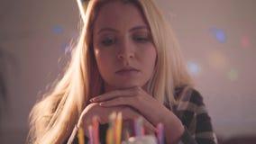 Eenzame droevige meisjeszitting voor weinig cake met aangestoken niet kaarsen De ongelukkige vrouw heeft verjaardagspartij Concep stock footage