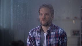 Eenzame droevige mens die op middelbare leeftijd door regenachtig venster, slechte weersomstandigheden kijken stock videobeelden
