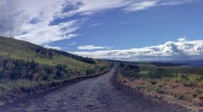 Eenzame en verre ruwe weg, Piilani Hwy voorbij Hana rond zuiden van Maui met de berg, de oceaan en de wolken van Haleakala op ach royalty-vrije stock foto's