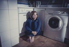 Eenzame en zieke vrouwenzitting op keukenvloer in spanningsdepressie en droefheid stock foto
