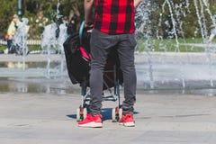 Eenzame enige vader hipster in geruit rood en zwart overhemd met een wandelwagen die in het stadspark lopen royalty-vrije stock fotografie