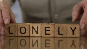 Eenzame, hogere mens die woord van houten kubussen, mensen in pensioneringshuis maken stock video