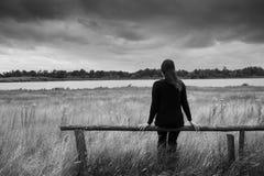 Eenzame jonge gedeprimeerde droevige vrouwenzitting op een houten straal of omheiningsverglazing in de afstand Zwart-wit portret stock fotografie