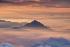 Eenzame kegelvormige berg boven ochtendmist en wolken stock fotografie