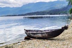Eenzame kleine boot op de rand van het maninjaumeer royalty-vrije stock foto