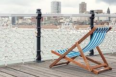 Eenzame kleurrijke deckchair bij kust met aardige mening aan het overzees en de stad van Brighton Stock Fotografie