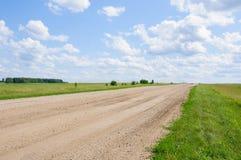 Eenzame landweg die aan de horizon achteruitgaan Stock Afbeeldingen