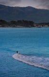 Eenzame langzame surfer op een golf stock afbeelding