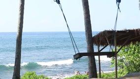 Eenzame lege Schommeling op de Aardachtergrond Tropisch eiland Bali, Indonesië Dichtbij het strand met zwart zand amazing stock video