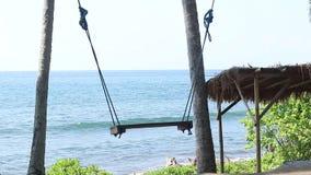 Eenzame lege Schommeling op de Aardachtergrond Tropisch eiland Bali, Indonesië Dichtbij het strand met zwart zand amazing stock footage