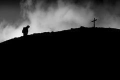 Eenzame leurder op de bovenkant van de berg Het lopen aan het kruis royalty-vrije stock fotografie