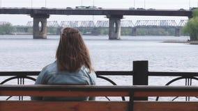 Eenzame meisjeszitting op de bank in het park en het kijken op het industriële landschap stock videobeelden