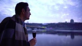 Eenzame mens in deken die zich dichtbij de de rivier en het drinken alcohol bevinden stock video