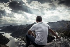 Eenzame mens die met hoop naar horizon op bergpiek met dramatisch zonlicht tijdens zonsondergang met effect van licht aan het ein stock afbeelding
