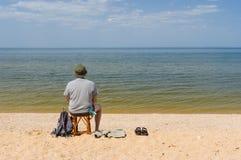Eenzame mensenzitting door de rivier van Dniepr royalty-vrije stock foto